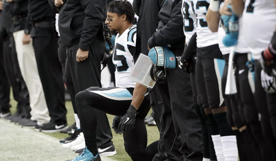 Carolina Panthers strong safety Eric Reid, center, takes a knee during the playing of the national anthem prior to an NFL football game against the Philadelphia Eagles, Sunday, Oct. 21, 2018, in Philadelphia. (AP Photo/Matt Rourke)