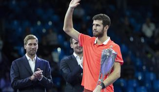 Karen Khachanov of Russia, right, holds the trophy after winning the final match of the Kremlin Cup tennis tournament against Adrian Mannarino of France in Moscow, Russia, Sunday, Oct. 21, 2018. (AP Photo/Pavel Golovkin)