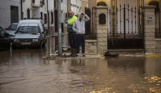 People observe flood water at their doorstep at the village of Campillos, Spain, where heavy rain and floods have caused severe damage and the death of a firefighter according to Spanish authorities Sunday, Oct. 21 2018.  Emergency services for the southern region of Andalusia say that the firefighter went missing when his truck overturned on a flooded road during heavy rains that fell through the night, and his body was found after a search Sunday morning. (AP Photo/Javier Fergo)