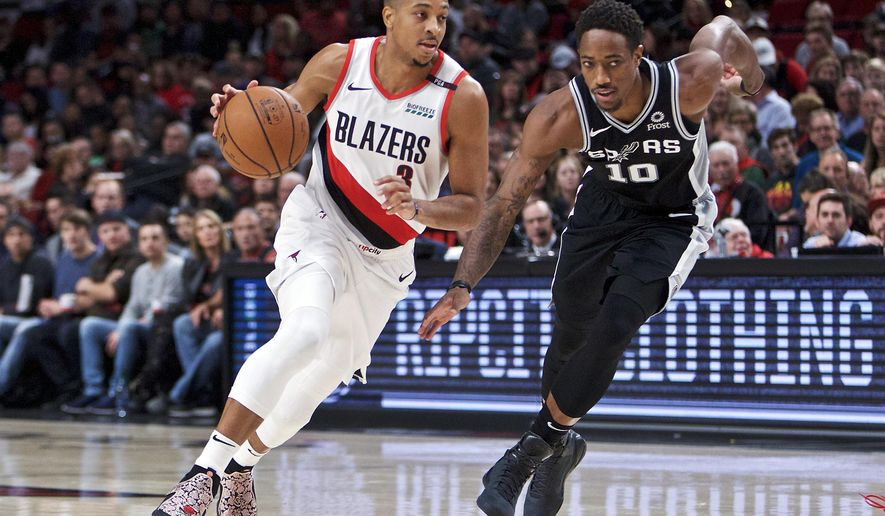 Portland Trail Blazers guard CJ McCollum, left, dribbles past San Antonio Spurs guard DeMar DeRozan during the first half of an NBA basketball game in Portland, Ore., Saturday, Oct. 20, 2018. (AP Photo/Craig Mitchelldyer)