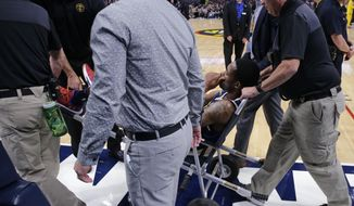 Denver Nuggets guard Will Barton is carted off the court after being injured during the third quarter of an NBA basketball game against the Phoenix Suns, Saturday, Oct. 20, 2018, in Denver. (AP Photo/Jack Dempsey)