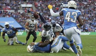 Tennessee Titans quarterback Marcus Mariota (8), center, goes over for a touchdown which was later disallowed during the second half of an NFL football game against Los Angeles Chargers at Wembley stadium in London, Sunday, Oct. 21, 2018. (AP Photo/Tim Ireland)