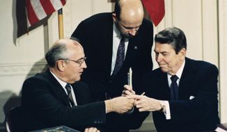 In this Dec. 8, 1987, file photo U.S. President Ronald Reagan, right, and Soviet leader Mikhail Gorbachev exchange pens during the Intermediate Range Nuclear Forces Treaty signing ceremony in the White House East Room in Washington, D.C. Gorbachev's translator Pavel Palazhchenko stands in the middle. (AP Photo/Bob Daugherty, File)