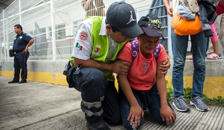 A migrant is comforted by a paramedic as the caravan of Central American migrants continues on a quest to reach the U.S. border. (Associated Press)