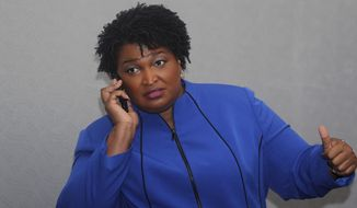 Georgia gubernatorial candidate Stacey Abrams answers her phone before speaking at the National Association of Black Journalists, Friday, Aug. 3, 2018, in Detroit. (AP Photo/Carlos Osorio)