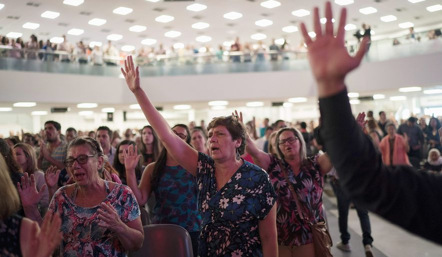 In this Sept. 2, 2018, file photo, evangelicals raise their hands in prayer as they listen to a song during a service at the Assembly of God Victory in Christ Church in Rio de Janeiro, Brazil.  (AP Photo/Leo Correa) **FILE**