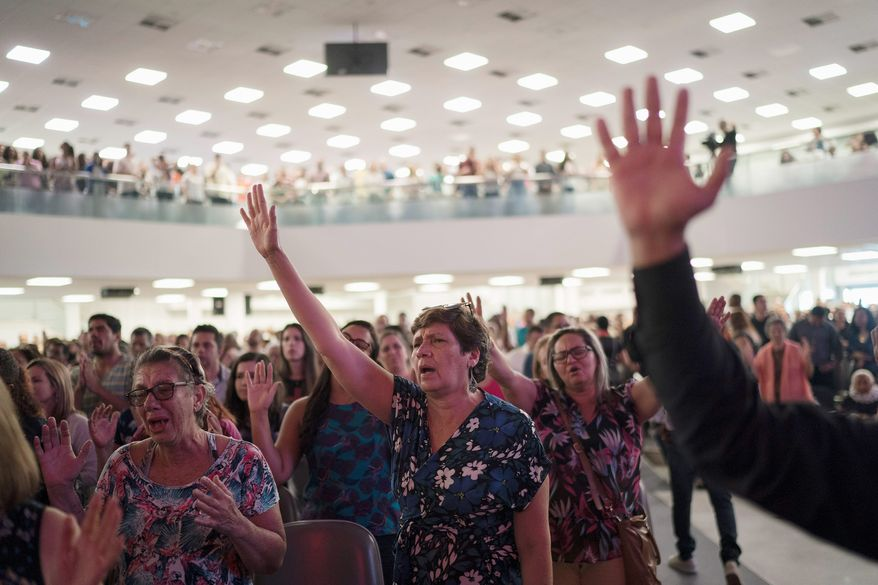 In this Sept. 2, 2018, photo, evangelicals raise their hands in prayer as they listen to a song during a service at the Assembly of God Victory in Christ Church in Rio de Janeiro, Brazil. In a Brazilian presidential election marked by uncertainties, there is little doubt about one thing: Evangelical voters will have a major impact. (AP Photo/Leo Correa)