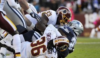 Dallas Cowboys running back Ezekiel Elliott (center) is tackled by Washington Redskins free safety D.J. Swearinger (bottom) and defensive end Jonathan Allen (top) during an NFL football game between the Dallas Cowboys and Washington Redskins, Sunday, Oct. 21, 2018, in Landover, Md. (AP Photo/Mark Tenally) **FILE**