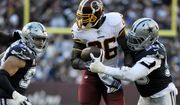 Washington Redskins running back Adrian Peterson (center) is tackled by Dallas Cowboys defensive end Demarcus Lawrence (right) during an NFL football game between the Dallas Cowboys and Washington Redskins, Sunday, Oct. 21, 2018, in Landover, Md. (AP Photo/Mark Tenally) ** FILE **