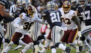 Dallas Cowboys running back Ezekiel Elliott (center) rushes the ball against Washington Redskins free safety D.J. Swearinger (left) and defensive end Jonathan Allen (right) during an NFL football game between the Dallas Cowboys and Washington Redskins, Sunday, Oct. 21, 2018, in Landover, Md. (AP Photo/Mark Tenally) **FILE**