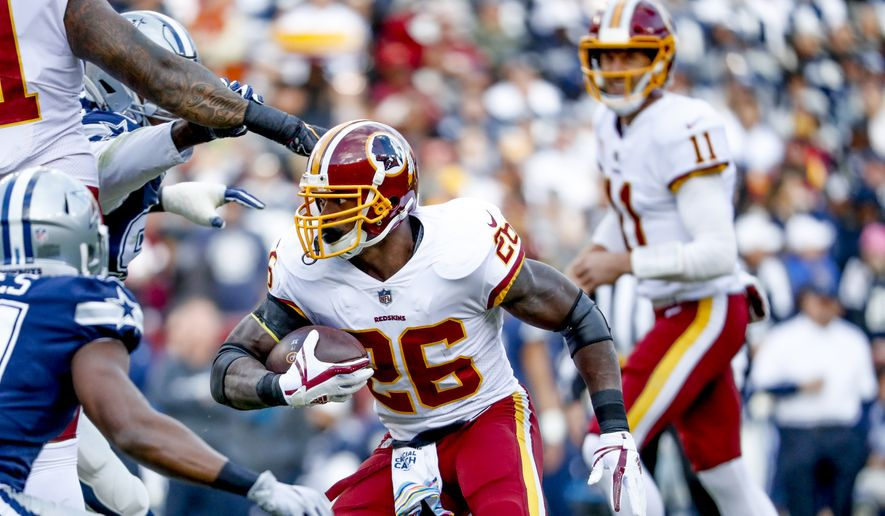 Washington Redskins quarterback Alex Smith (11) hands off to Washington Redskins running back Adrian Peterson (26) during the first quarter of an NFL football game against the Dallas Cowboys, Sunday, Oct. 21, 2018, in Landover, Md. The Redskins defeated the Cowboys 20-17. (AP Photo/Andrew Harnik) **FILE**