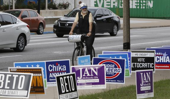 Gene Lantz rides pass candidates sign near the George L. Allen, Sr. Courts Building in Dallas on Monday, Oct. 22, 2018, on his way to a voting rally on the opening day of early voting across the State of Texas. Early voting starts Oct. 22 and ends Nov. 2. (Irwin Thompson/The Dallas Morning News via AP)
