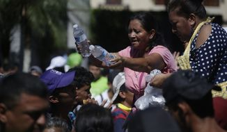Residents hand out water bottles and sandwiches to Central American migrants making their way to the U.S. in a large caravan, at the main plaza in Tapachula, Mexico, Monday, Oct. 22, 2018.  Thousands of Central American migrants hoping to reach the U.S. were deciding Monday whether to rest in this southern Mexico town or resume their arduous walk through Mexico as President Donald Trump rained more threats on their governments. (AP Photo/Moises Castillo)