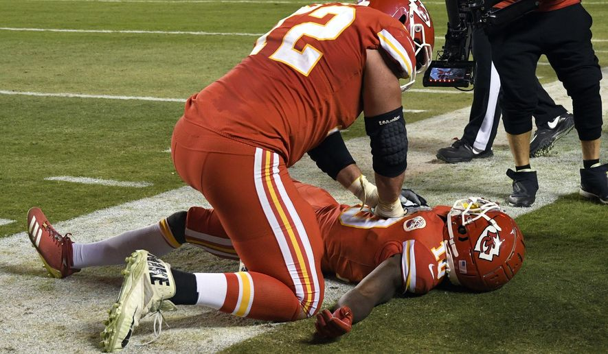 Kansas City Chiefs offensive lineman Eric Fisher (72) pretends to do CPR on wide receiver Tyreek Hill (10) after Hill scores a touchdown during the second half of an NFL football game against the Cincinnati Bengals in Kansas City, Mo., Sunday, Oct. 21, 2018. The Chiefs won, 45-10. (AP Photo/Reed Hoffmann)