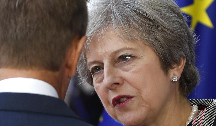 British Prime Minister Theresa May, right, speaks with European Council President Donald Tusk after a group photo an EU-ASEM summit in Brussels, Friday, Oct. 19, 2018. EU leaders met with their Asian counterparts Friday to discuss trade, among other issues. (AP Photo/Alastair Grant)