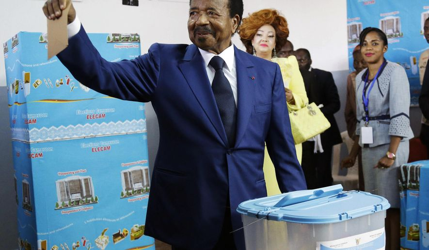 FILE- In this Sunday Oct. 7, 2018 file photo, Cameroon's Incumbent President Paul Biya, of the Cameroon People's Democratic Movement party, casts his vote during the Presidential elections in Yaounde, Cameroon. Africa's oldest president, Cameroon's Paul Biya, easily won a seventh term on Monday Oct. 22, 2018 after a Constitutional Council he appointed rejected all legal challenges to the election. (AP Photo/Sunday Alamba, File)
