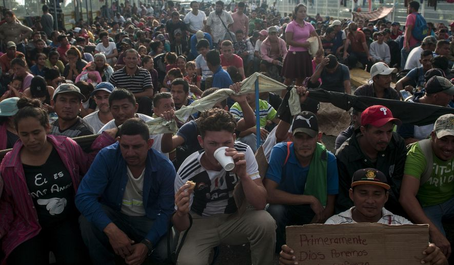 Honduras migrants wait to be attended by Mexican migration authorities on a bridge that stretches over the Suchiate River, connecting Guatemala and Mexico, in Tecun Uman, Guatemala, Sunday, Oct. 21, 2018. Despite Mexican efforts to stop them at the border, about 5,000 Central American migrants resumed their advance toward the U.S. border early Sunday in southern Mexico. (AP Photo/Oliver de Ros)