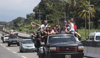 Central American migrants making their way to the U.S. in a large caravan fill the truck of a driver who offered them the free ride, as they arrive to Tapachula, Mexico, Sunday, Oct. 21, 2018. Despite Mexican efforts to stop them at the Guatemala-Mexico border, about 5,000 Central American migrants resumed their advance toward the U.S. border Sunday in southern Mexico. (AP Photo/Moises Castillo)