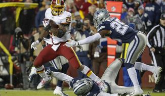Washington Redskins running back Adrian Peterson (26) is chased by Dallas Cowboys free safety Xavier Woods (25) during the second half of an NFL football game, Sunday, Oct. 21, 2018 in Landover, Md. (AP Photo/Andrew Harnik)