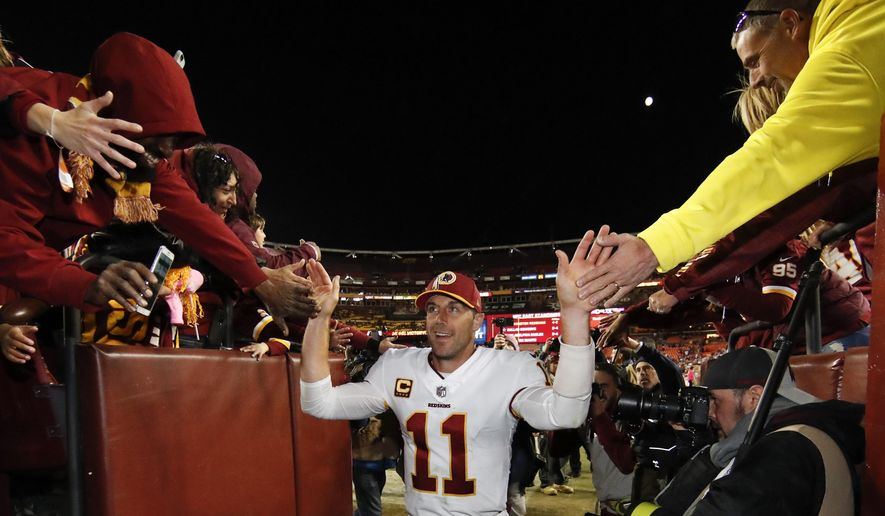 Washington Redskins quarterback Alex Smith (11) celebrates with fans after an NFL football game against the Dallas Cowboys, Sunday, Oct. 21, 2018 in Landover, Md. (AP Photo/Alex Brandon)