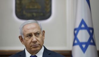 FILE -In this Oct. 7, 2018 file photo, Israel Prime Minister Benjamin Netanyahu attends the weekly cabinet meeting at his office in Jerusalem. On Sunday, Oct, 21, 2018, Netanyahu postponed the planned demolition of a West Bank hamlet to allow time for a negotiated solution with its residents. Israel has come under heavy criticism, with major European countries urging it to avoid the demolition of Khan al-Ahmar. The International Criminal Court's chief prosecutor recently said such a move could constitute a war crime. (Abir Sultan/Pool via AP, File)