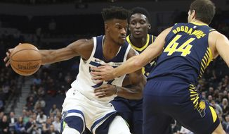 Minnesota Timberwolves' Jimmy Butler, left, tries to work between Indiana Pacers' Victor Oladipo, center, and Bojan Bogdanovic, of Croatia, in the first half of an NBA basketball game Monday, Oct. 22, 2018, in Minneapolis. (AP Photo/Jim Mone)