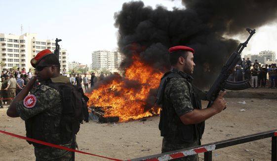 Hamas security forces stand guard while they burn some 1,383 bars of hashish and 1,242,000 pills of Tramadol, that have been seized since the beginning of the year, before they burn it, in Gaza City, Monday, Oct. 22, 2018. (AP Photo/Adel Hana)