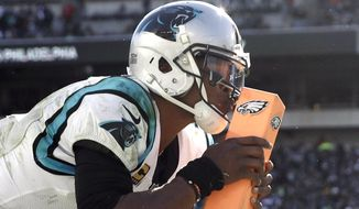 Carolina Panthers quarterback Cam Newton kisses the pylon after tripping over it while celebrating a touchdown pass to tight end Greg Olsen during the second half of an NFL football game against the Philadelphia Eagles, Sunday, Oct. 21, 2018, in Philadelphia. (AP Photo/Matt Rourke)