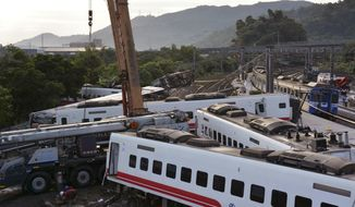 Rescue workers work at the site of a train derailment in Yilan county northeastern Taiwan Monday, Oct. 22, 2018. Passengers were killed and injured on Sunday when one of Taiwan's newer, faster trains derailed on a curve along a popular weekend route, officials said.(Kyodo News via AP)