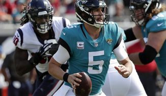 Blake Bortles (5) looks for a receiver as he is pressured by Houston Texans linebacker Jadeveon Clowney, back left, during the first half of an NFL football game, Sunday, Oct. 21, 2018, in Jacksonville, Fla. (AP Photo/John Raoux)