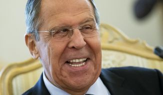 Russian Foreign Minister Sergey Lavrov smiles as he speaks to Madagascar's Foreign Minister Eloi Maxime Alphonse Dovo during their meeting in Moscow, Russia, Monday, Oct. 22, 2018. Lavrov will meet with U.S. National Security Adviser John Bolton for high-tension talks in Moscow, after President Donald Trump announced his intention to withdraw from a landmark nuclear weapons treaty. (AP Photo/Alexander Zemlianichenko)