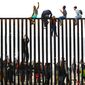 Migrants sit on top of a wall near San Diego earlier this year during a gathering that included people who live on both sides of the border. (Associated Press)