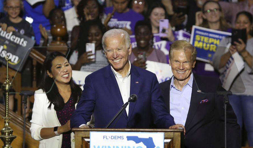 Rep. Stephanie Murphy, former Vice President Joe Biden and Sen. Bill Nelson respond to cheering supporters as Biden headlined a rally for Democrats in downtown Orlando, Fla., Tuesday, Oct. 23, 2018. Floridians go to the polls for the midterm election in two weeks. (Joe Burbank/Orlando Sentinel via AP)