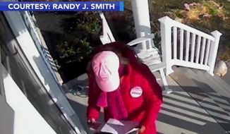 Monique Johns, a Democratic Party candidate for Delaware state representative, is caught on camera stealing her opponent's campaign material from the front door of a suburban household. (Image: ABC-6 Philadelphia video screenshot)