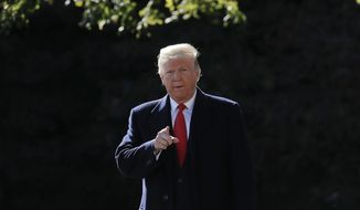 President Donald Trump points as he walks over to make remarks to members of the media on the South Lawn of the White House in Washington, Monday, Oct. 22, 2018, before boarding Marine One helicopter for a short trip to Andrews Air Force Base, Md., en route to Houston. (AP Photo/Pablo Martinez Monsivais)