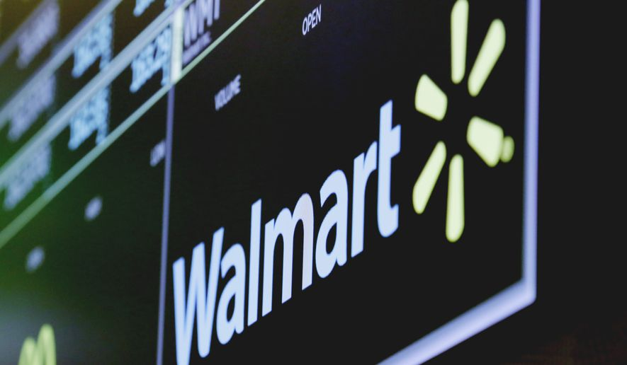 In this May 17, 2018, file photo, the logo for Walmart appears above a trading post on the floor of the New York Stock Exchange. Walmart Inc. is making two improvements to its third-party marketplace heading into the holidays as it seeks to better compete with online leader Amazon.com. (AP Photo/Richard Drew, File)