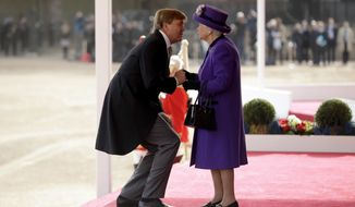 Netherlands' King Willem-Alexander bends down to kiss Britain's Queen Elizabeth II as she greets him upon his arrival to inspect an honour guard during a Ceremonial Welcome on Horse Guards Parade in London, Tuesday, Oct. 23, 2018. Dutch King Willem-Alexander and Queen Maxima are on a State Visit to Britain. (AP Photo/Matt Dunham, Pool)