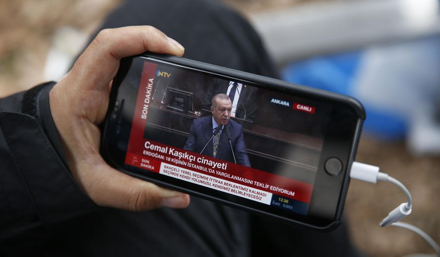 A journalist covering the killing of Saudi writer Jamal Khashoggi, watches a live transmission of Turkey's President Recep Tayyip Erdogan addressing members of his ruling Justice and Development Party (AKP), at the parliament in Ankara, Turkey, Tuesday, Oct. 23, 2018. Turkey's president says Saudi officials started planning to murder Saudi writer Jamal Khashoggi days before his death in Saudi Arabia's Istanbul consulate. (AP Photo/Lefteris Pitarakis)