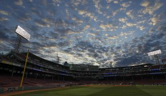 Clouds fill the sky over Fenway Park as the Los Angeles Dodgers practice for Game 1 of the World Series baseball game against the Boston Red Sox Monday, Oct. 22, 2018, in Boston. (AP Photo/Matt Slocum)