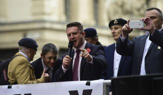 Former English Defence League (EDL) leader Tommy Robinson addresses his supporters as he arrives at the Old Bailey where he is accused of contempt of court, in London, Tuesday, Oct. 23, 2018. A judge has referred a contempt-of-court case involving far-right activist Stephen Yaxley-Lennon to Britain's attorney general for consideration. Yaxley-Lennon, who uses the pseudonym Tommy Robinson, was jailed in May for potentially prejudicing a trial after broadcasting live on Facebook outside the trial of men accused of sexually abusing teenage girls. (David Mirzoeff/PA via AP)
