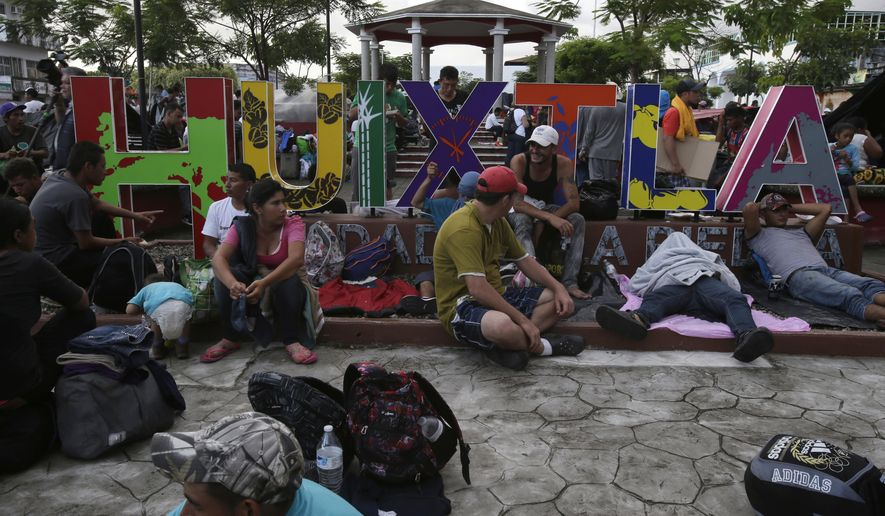 Central American migrants making their way to the U.S. rest in a park after arriving to Huixtla, Mexico, Monday, Oct. 22, 2018. Thousands of Central American migrants resumed an arduous trek toward the U.S. border Monday, with many bristling at suggestions there could be terrorists among them and saying the caravan is being used for political ends by U.S. President Donald Trump. (AP Photo/Moises Castillo)
