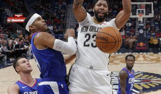 New Orleans Pelicans forward Anthony Davis (23) slam dunk over Los Angeles Clippers forward Tobias Harris and forward Danilo Gallinari, left, in the first half of an NBA basketball game in New Orleans, Tuesday, Oct. 23, 2018. (AP Photo/Gerald Herbert)
