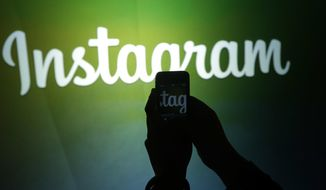 In this June 20, 2013 file photo, a journalist makes a video of the Instagram logo using the new video feature at Facebook headquarters in Menlo Park, Calif. Facebook bought Instagram for $1 billion back in 2012. (AP Photo/Marcio Jose Sanchez, File)