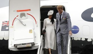 Britain's Prince Harry and Meghan, Duchess of Sussex disembark from their plane on their arrival in Suva, Fiji, Tuesday, Oct. 23, 2018. Prince Harry and his wife Meghan are on day eight of their 16-day tour of Australia and the South Pacific.(AP Photo/Kirsty Wigglesworth,Pool)