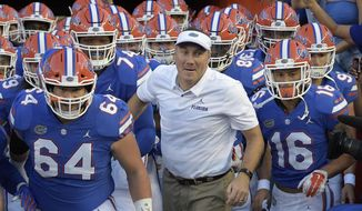 FILE - In this Sept. 1, 2018, file photo, Florida head coach Dan Mullen, center, runs onto the field with his players before an NCAA college football game against Charleston Southern, in Gainesville, Fla. With Mullen leading the way and calling the plays, No. 9 Florida has made more offensive improvements in the last nine months than it did in the previous nine years. The biggest strides have come in the last seven weeks, all since losing to Kentucky for the first time since 1986. (AP Photo/Phelan M. Ebenhack, File)