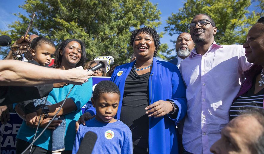 Surrounded by family and supporters, Georgia gubernatorial candidate Stacey Abrams speaks with the press after casting her early ballot at The Gallery at South DeKalb Mall in Decatur, Monday, October 22, 2018. Today marks only 15 days left until Election Day on Tuesday, November 6.  (Alyssa Pointer/Atlanta Journal-Constitution via AP)