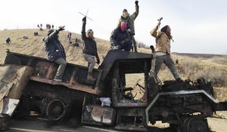 FILE - In this Nov. 21, 2016, file photo, protesters against the Dakota Access oil pipeline stand on a burned-out truck near Cannon Ball, N.D. In a lawsuit filed, Friday, Oct. 19, 2018, two members of the Standing Rock Sioux tribe and a reservation priest are suing over a five-month shutdown of a North Dakota highway during protests against oil pipeline, saying the closure violated their and others' constitutional rights. (AP Photo/James MacPherson, File)