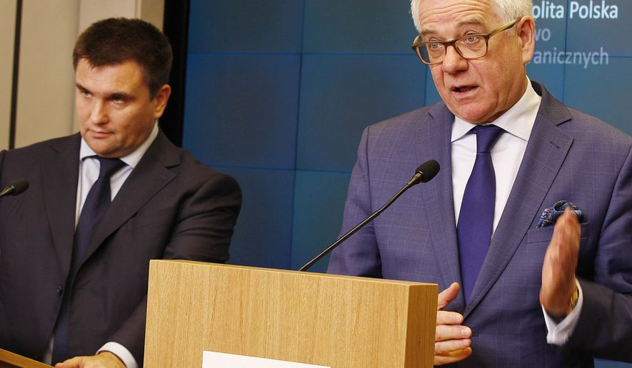 Ukraine's Foreign Minister Pavlo Klimkin, left, and his Polish counterpart Jacek Czaputowicz, right, address the media in Warsaw, Poland, Tuesday, Oct. 23, 2018, following talks on security and Russia's hostile activity, and announced that Poland has awarded Ukrainian filmmaker Oleg Sentsov, imprisoned in Russia, for his opposition to Russia's seizure of the Crimea Peninsula. (AP Photo/Czarek Sokolowski)