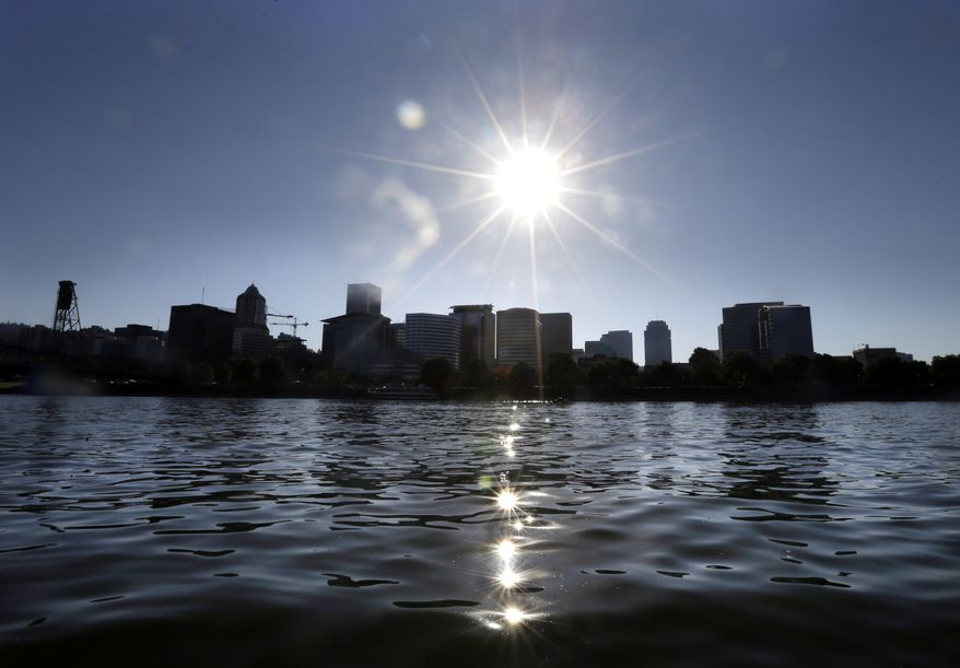 FILE - In this July 6, 2017, file photo, late afternoon sun sparkles off the Willamette River in Portland, Ore. The U.S. Environmental Protection Agency is proposing to scale back the scope and cost of a planned $1 billion cleanup of the Portland Harbor superfund site because the agency says new research shows one contaminant is less toxic than previously thought, reducing the cost of the project by $35 million. (AP Photo/Don Ryan, File)