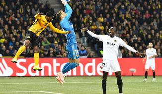 YB's Roger Assale, left, fights for the ball with Valencia's goalkeeper Norberto Murara Neto, center, as Mouctar Dikahaby, looks on during the Champions League group stage group H soccer match between Switzerland's BSC Young Boys Bern and Spain's Valencia CF, at the Stade de Suisse Stadium in Bern, Switzerland, Tuesday, Oct. 23, 2018. (Peter Schneider/Keystone via AP)